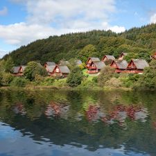 Holiday lodges on hillside viewed from the loch